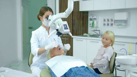 Dentist looks at womans teeth with a dental equipment