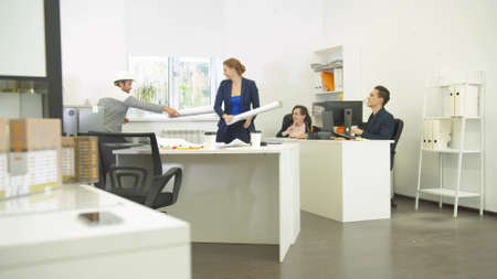 Man in helmet and woman play with whatmans, their workmates laugh at them in the office