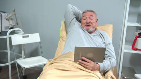 Man lie on bed in the hospital and talk with someone on the tablet Stock Photo