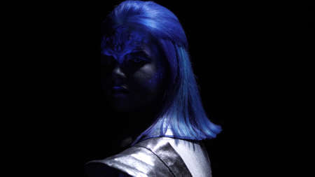 Alien with blue hair and skin looks at the camera