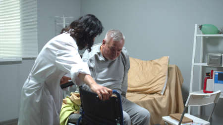Doctor in uniform help old man to sit in a wheelchair in hospital