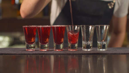 Close up, bartender pours alcohol in shot glasses one by one at the bar Banco de Imagens