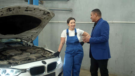 Slow motion, woman in uniform shows a car to the owner
