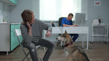 Slow motion, man with husky talks on phone in cabinet of vet