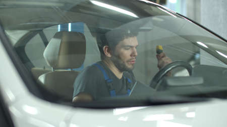 Mechanic with a tablet sits in a car and checks it Banco de Imagens
