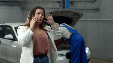 Mechanic repairs a car, sad woman talks on phone emotionally Banco de Imagens