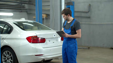 Mechanic with a tablet inspects a car