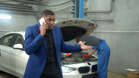 Man talks on phone emotionally, mechanic repairs a car on the background