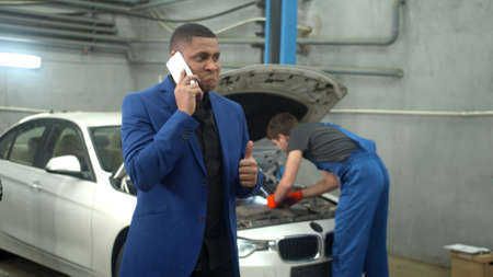 Man talks on phone, mechanic repairs a car on the background, slow motion
