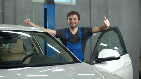 Slow motion, mechanic is standing near a car and smiling Banco de Imagens