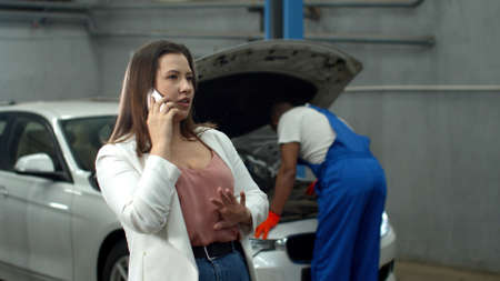 Mechanic repairs a car, woman talks on phone