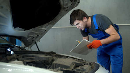 Mechanic examines the motor of car and takes notes