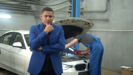 Man in suit shows discontent at the camera, mechanic repairs a car on the background Banco de Imagens
