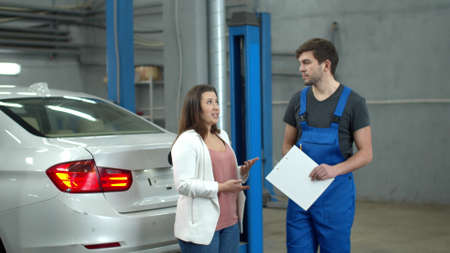 Woman discusses the price of a car repair with a mechanic