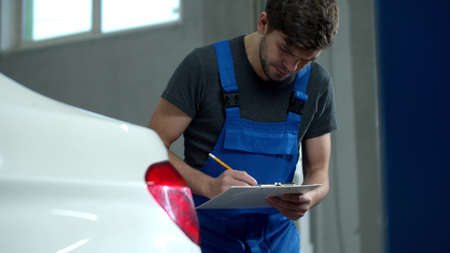 Mechanic inspects the headlights of a car and writes something Banco de Imagens