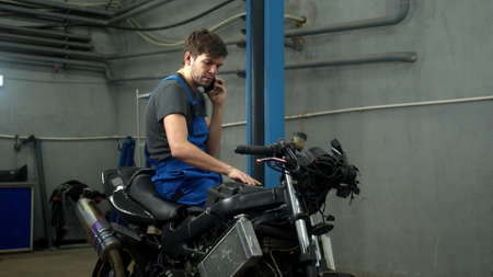 Technician sits on motorcycle and talks on phone