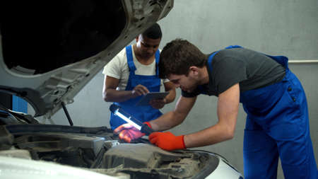 Mechanic with flashlight examines the motor of car and his collegue takes notes Banco de Imagens