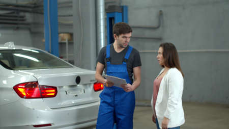 Mechanic discusses the price of a car repair with woman