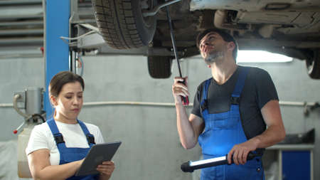 Mechanic shows a car wheels, woman with tablet takes notes