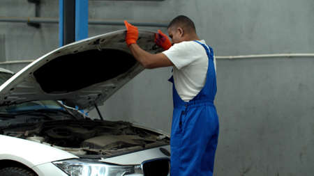 Mechanic opens the hood of a car and looks at the motor Foto de archivo