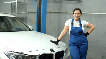 Woman mechanic closes hood of car and smiles in car service