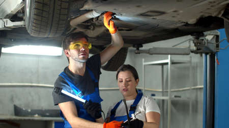 Mechanic in glasses repairs a car, woman holds a flashlight