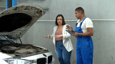 Woman discuss the motor of car with mechanic with tablet Banco de Imagens