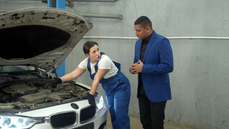 Woman technician shows a car to the owner in auto repair shop