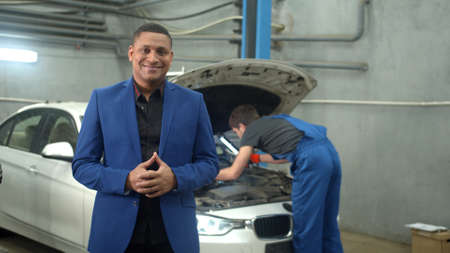 Man in suit smiles at the camera, mechanic repairs a car on the background