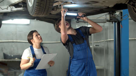 Mechanic with flashlight shows a car case, woman takes notes