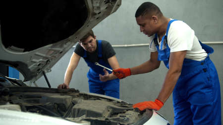 Mechanics in uniform repair the motor of car, slow motion