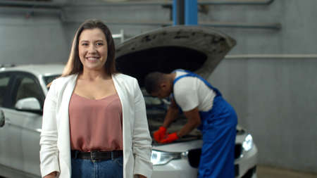 Mechanic repairs a car, woman smiles at the camera