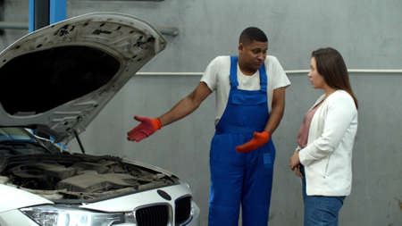 Mechanic shows the motor of car to woman