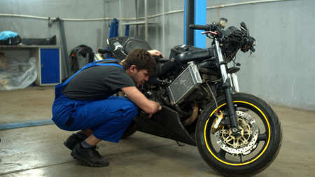 Mechanic examines a motorcycle in auto repair shop