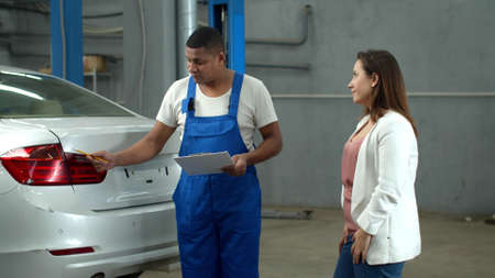 Mechanic shows car damage to a woman
