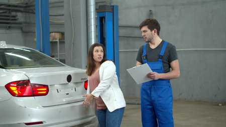 Woman shows to mechanic the zones of a bang on a car Banco de Imagens