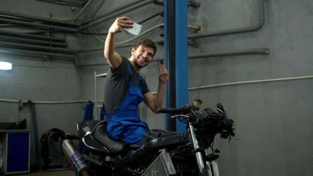 Technician sits on motorcycle and makes a photo