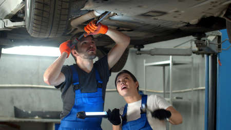 Slow motion, mechanic in gloves repairs a car, woman holds a flashlight Banco de Imagens