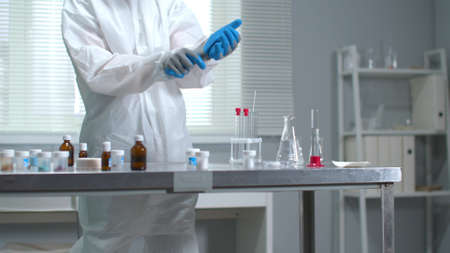 Man in protective workwear put on medical gloves in the laboratory