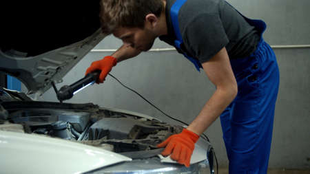 Slow motion, mechanic opens the hood of a car and turns on a flashlight