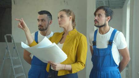 Woman explains to repairmen a work plan Stock fotó
