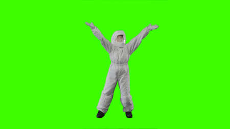 Girl in a spacesuit jumps and waves her hands on a green background