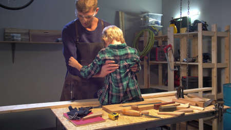 Man puts boy on the board in the workshop