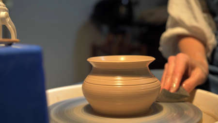 Woman makes a pot with stick on a pottery wheel in a workshop, slow motion