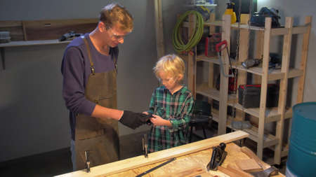 Little boy puts on protective gloves in the workshop