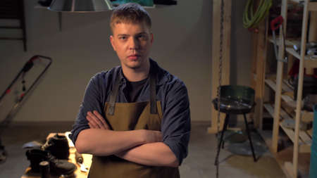 Man in apron stands and looks at the camera