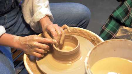 Little boy and woman makes a pot with pottery wheel in a workshop 版權商用圖片