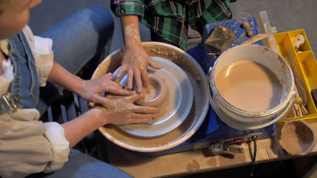 Slow motion, woman sits and works with pottery wheel in a workshop