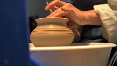 Woman makes a pot with stick on a pottery wheel in a workshop