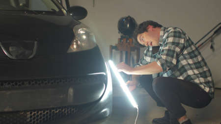 A motorist inspects a car in a garage with a special lamp and talking on the phone Stock Photo